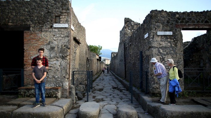 Tourists look down an ancient Roman cobbled street at the UNESCO World Heritage site of Pompeii,