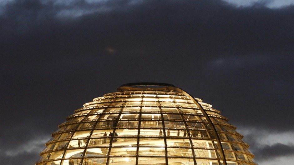 People walk inside the cuppola of the Reichstag building, the seat of the lower house of parliament Bundestag during sunset in Berlin