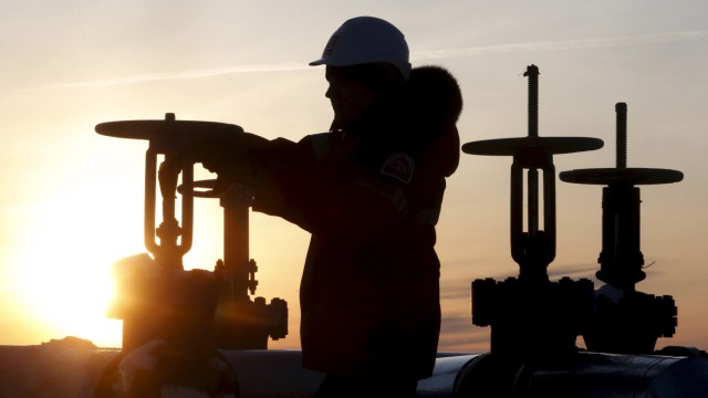 File photo of a worker checking valve of oil pipe at Lukoil company owned Imilorskoye oil field outside West Siberian city of Kogalym