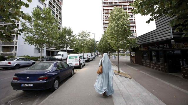 Chehrazad walks down a street in Mantes-la-Jolie, a suburb of Paris