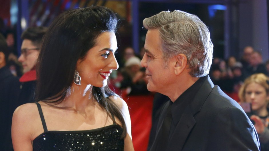 Cast member Clooney and his wife Amal arrive on red carpet for screening at opening gala of 66th Berlinale International Film Festival in Berlin