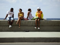 Youths sit on Havana's El Malecon seafront bolulevard