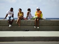 Youths sit on Havana's El Malecon seafront bolulevard