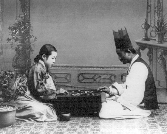 Korea: A man and a woman playing a game of <i>baduk</i> or 'go', c. 1910.