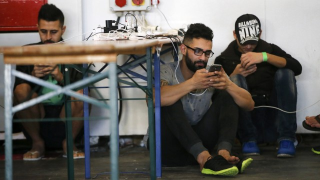 Migrants charge and use their smartphones in a temporary refugee shelter inside a hall of Berlin's fairground
