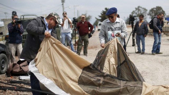 Meza, a lawyer representing drug lord Guzman, assembles a tent with Rivera, Human Rights Coordinator of Tamaulipas state, before starting hunger strike in support of Guzman, outside Altiplano Federal Penitentiary
