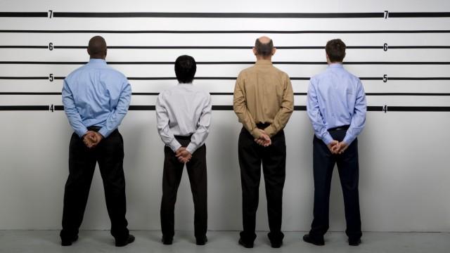 Multi-ethnic businessmen in police line up