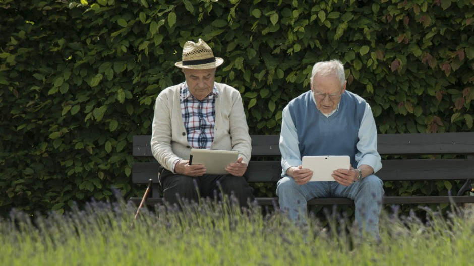 Two old men using tablet computers in the park model released PUBLICATIONxINxGERxSUIxAUTxHUNxONLY UU