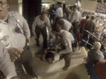 Handout of a still image taken from video of Rakeem Jones laying on the ground after being removed from his seat during Trump rally in Fayetteville