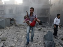 A man holds a girl who survived heavy shelling in the Douma neighborhood of Damascus