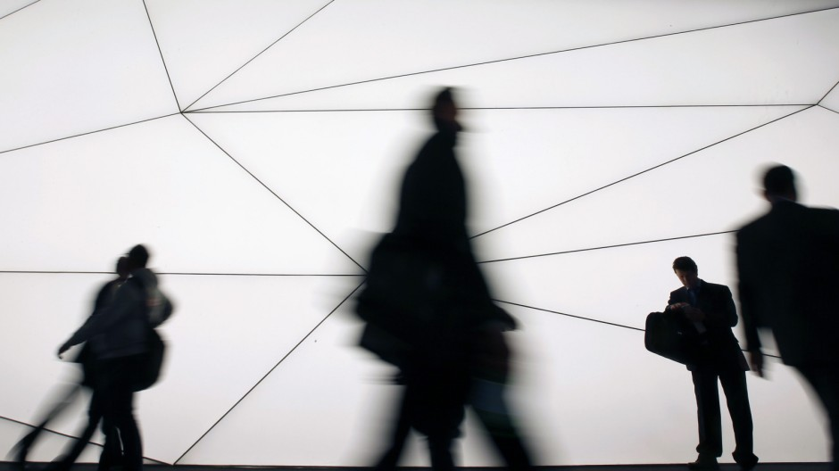 A man looks at his mobile as people walk past him at the Mobile World Congress in Barcelona