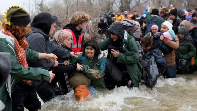 Frustrated Migrants Stranded On The Border Attempt To Walk In To Macedonia