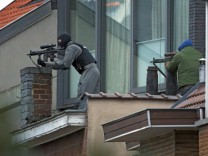 Masked Belgian police secure the area from a rooftop near the scene where shots were fired during a police search of a house in the suburb of Forest near Brussels