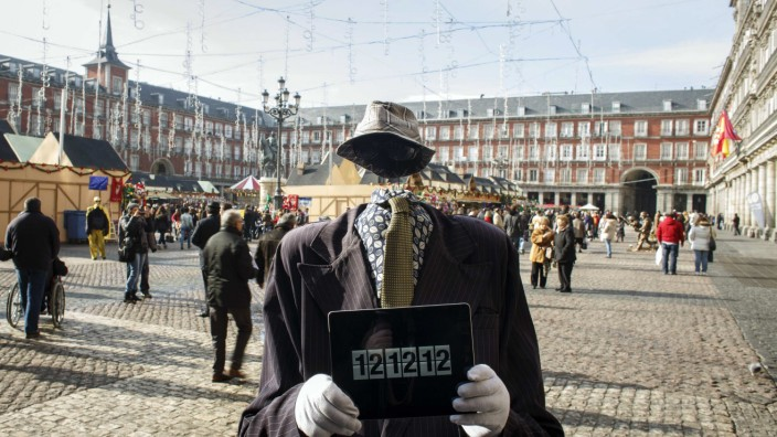 Street performer poses with iPad showing time of 12:12:12 in Madrid