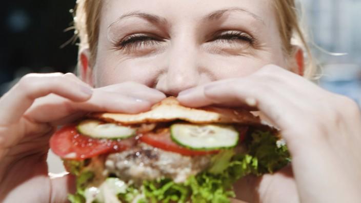 Young woman eating a hamburger model released PUBLICATIONxINxGERxSUIxAUTxHUNxONLY FEXF000039