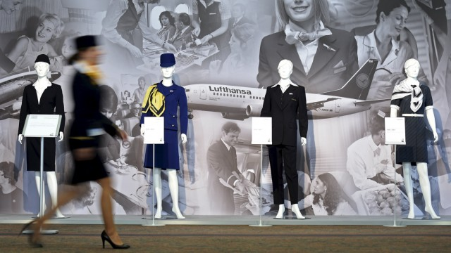 File photo of a Lufthansa flight attendant passing a row of mannequins dressed in historical flight uniforms at the annual shareholders meeting in Hamburg