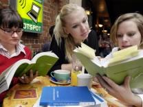 Drei Studentinnen zu Semesterbeginn mit Vorlesungsverzeichnis