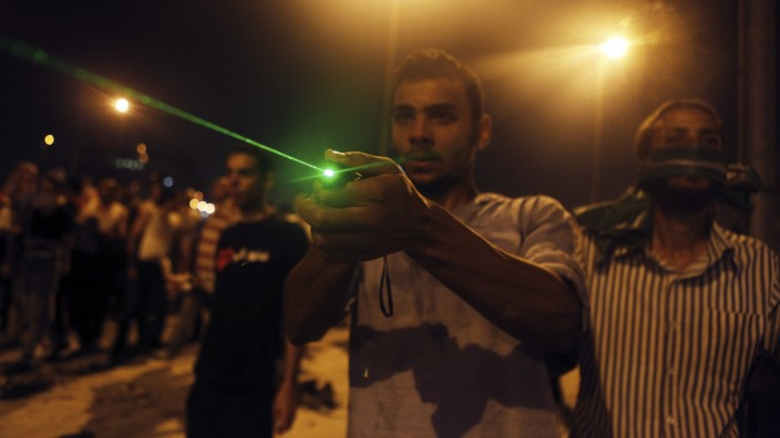 A supporter of deposed Egyptian President Mohamed Mursi flashes a laser light at riot police during clashes on the Sixth of October Bridge over the Ramsis square area in central Cairo
