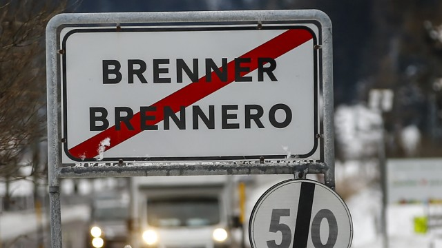 Cars drive along a street with a sign reading 'Brenner-Brennero' in the Italian village of Brenner on the Italian-Austrian border