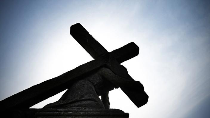 Jesusstatue unter Kreuz