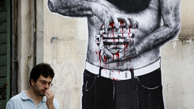 A man walks next to a mural depicting a hooded man holding the sign of the Euro in his bleeding hands in Athens