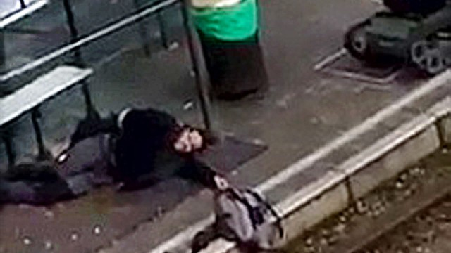 A suspect lies on the platform of a tramway station, in this image taken from amateur video, after he was shot and wounded by police in the Brussels borough of Schaerbeek, following Tuesday's bombings in Brussels,