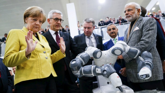 German Chancellor Merkel and Indian Prime Minister Modi look at a YuMi robotic arm at the world's largest industrial technology fair, the Hannover Messe, in Hanover