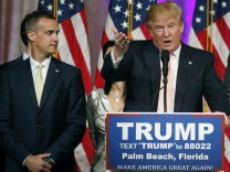 Campaign manager Corey Lewandowski stands next to Donald Trump during a news conference in Palm Beach, Florida