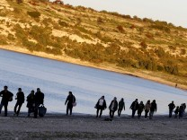 File photo of refugees walk along a beach before trying to travel to the Greek island of Chios from the western Turkish coastal town of Cesme