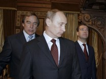 Russia's then President Medvedev, and then Prime Minister Putin listen to art director of St. Petersburg House of Music Roldugin