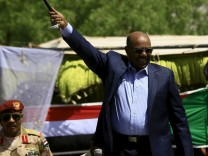 Sudanese President Omar Hassan al-Bashir waves to the crowd during a war torn Darfur peace campaign rally at Nyala in South Darfur