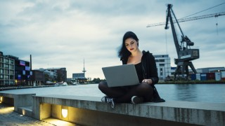 Germany, Muenster, young woman with laptop sitting in front of city harbour model released Symbolfot