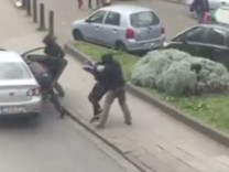 Police officers detain a suspect during a raid in which fugitive Mohamed Abrini was arrested in Anderlecht in this still image taken from video