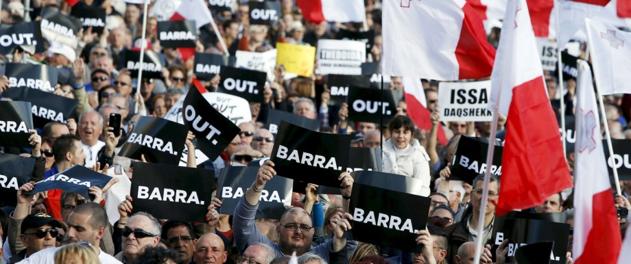 Protestors hold posters reading 'Out' during a demonstration calling on Maltese Prime Minister Joseph Muscat to resign after two members of his government were named in the Panama Papers leak scandal, outside the office of the Prime Minister in Valletta
