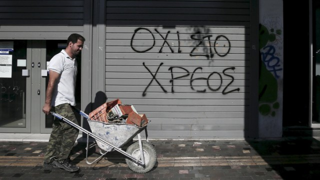 File photo shows graffiti on a closed Attica Bank branch reading, 'No to the debt' as a worker pushes a cart walks by in Athens