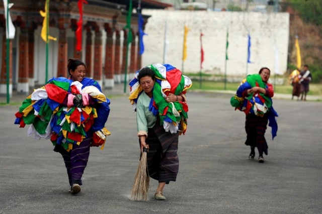Women carry flags in Tashichho Dzong, the seat of the head of Bhutan's Civil Government in Thimphu in preparation for the visit of Britain's Prince William and his wife Catherine the Duchess of Cambridge