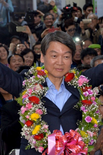 Ahn Cheol-soo, the minor opposition People's Party co-chairman, celebrates his victory in the parliamentary election at his office in Seoul