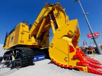 Visitors pose for a picture with a caterpillar at the 'Bauma' Trade Fair in Munich