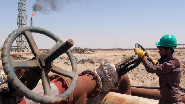 A worker checks the valve of an oil pipe at Al-Sheiba oil refinery in the southern Iraq city of Basra