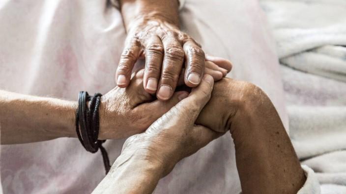 Altenpflege zuhause Pflegerin betreut Seniorin in ihrer Wohnung am Bett