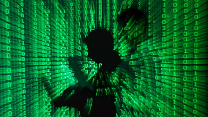 File illustration of a projection of binary code around the shadow of a man holding a laptop computer in an office in Warsaw