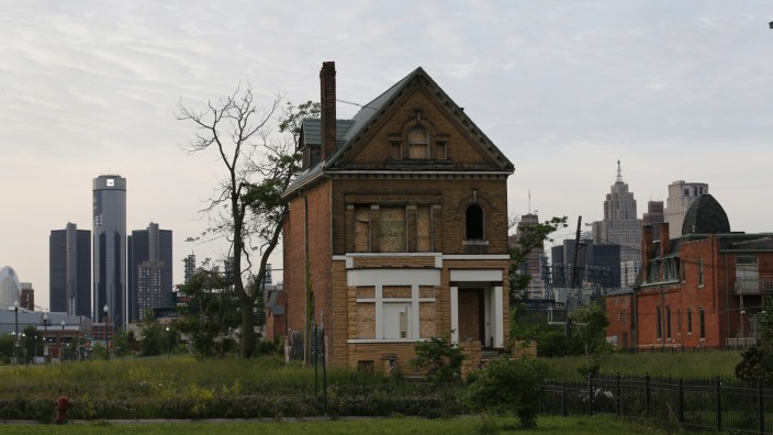 A boarded up vacant home is seen with General Motors World Headquarters and the Detroit skyline