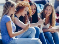Four friends sitting together on steps looking at smartphone model released Symbolfoto PUBLICATIONxI