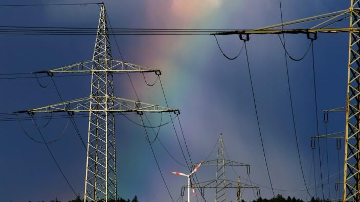 Regenbogen hinter Windrad und Stromleitungen