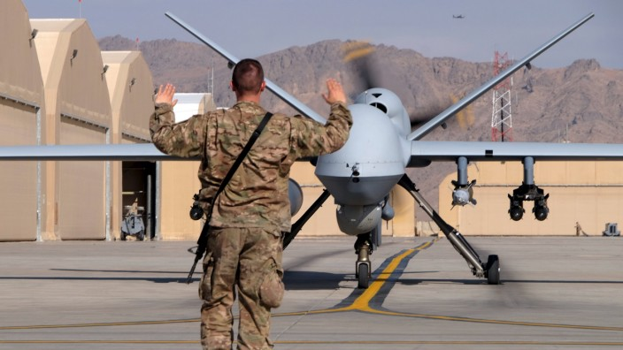A U.S. airman guides a U.S. Air Force MQ-9 Reaper drone as it taxis to the runway at Kandahar Airfield, Afghanistan