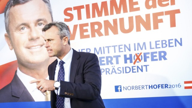 Presidential candidate Hofer presents his new electoral posters during a news conference in Vienna