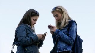Women use their smartphones in Kiev