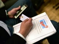 AfD-Delegierter mit dem Grundsatzprogramm der Partei