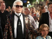 Chanel's head designer and creative director Karl Lagerfeld walks with a model after a fashion show of his latest inter-seasonal Cruise collection, at the Paseo del Prado street in Havana, Cuba