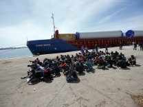 Migrants sit after disembarking from a merchant ship in the Sicilian harbour of Augusta